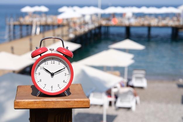 Red alarm clock at ten in morning against backdrop of beach resort