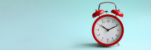 Red alarm clock on turquoise background shows