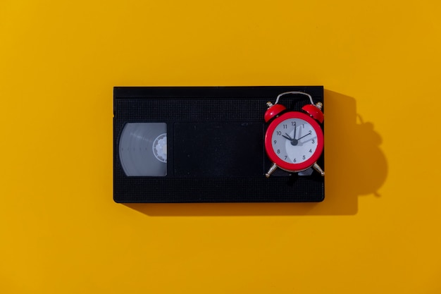 Red alarm clock and vhs cassette on yellow background