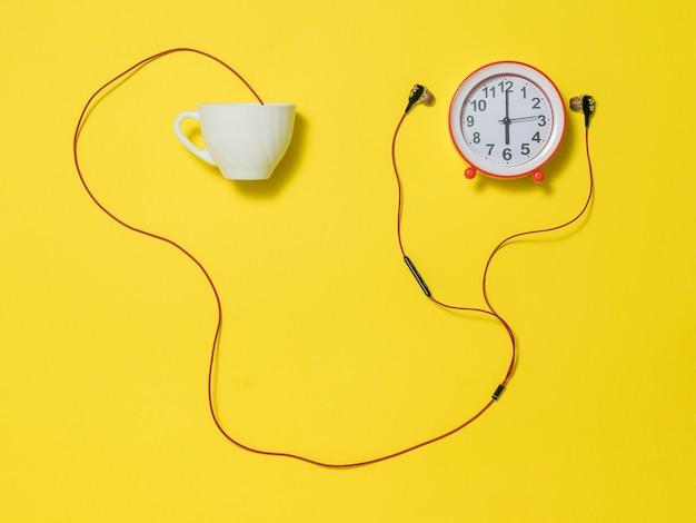 黄色の背景に赤い目覚まし時計、白いカップと赤いヘッドフォン。クリエイティブアートコラージュ。