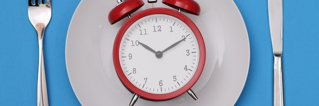 Red alarm clock on white plate. diet regimen and healthy lifestyle concept