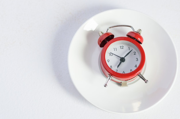 Red alarm clock on white plate with a silver spoon