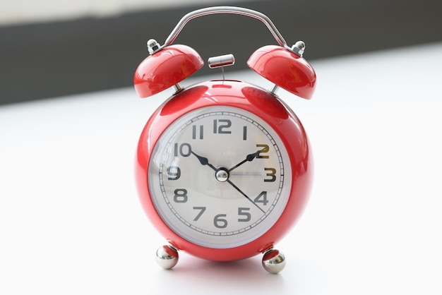 Red alarm clock on white table