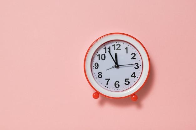 ピンクの背景に白い文字盤と赤い目覚まし時計。クラシックなアナログ時計。