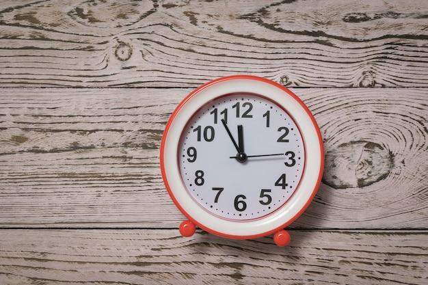 Красный будильник со стрелками на розовом деревянном фоне. классические аналоговые часы.