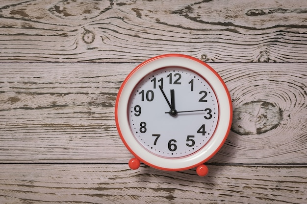 Red alarm clock with arrows on a pink wooden background. classic analog clock.