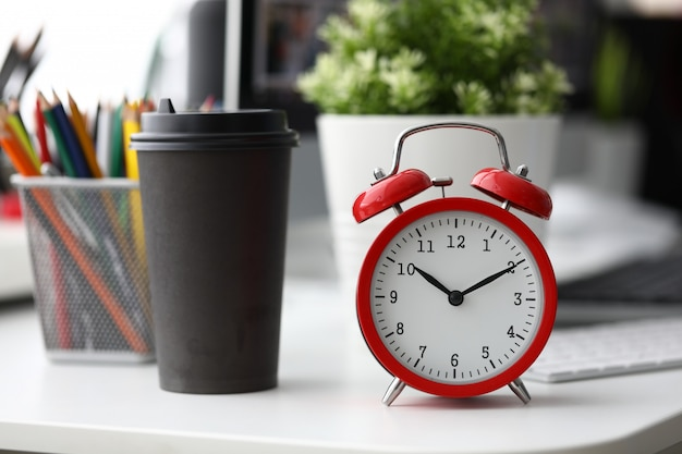 Red alarm clock with black paper coffee cup