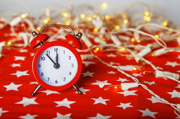 Red alarm clock with lights on a red fabric