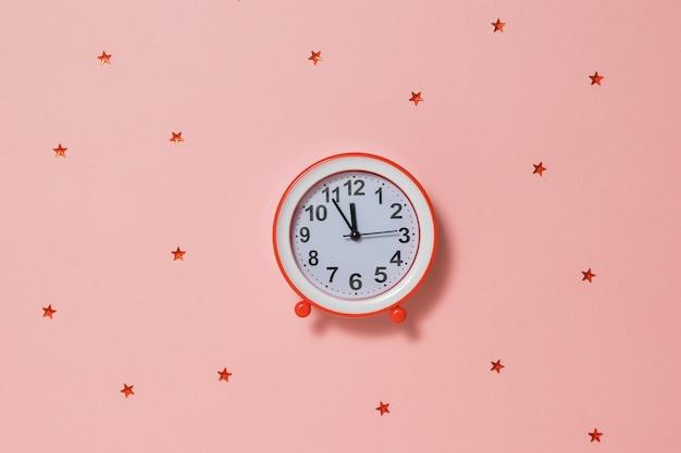 赤い背景に赤い星と赤い目覚まし時計。時計は休日が近づいていることを示しています。