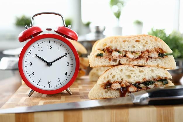 木製のテーブル背景に立っているサンドイッチと赤い目覚まし時計