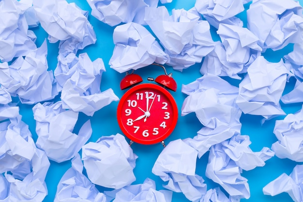 Red alarm clock with white crumpled paper balls on a blue background.