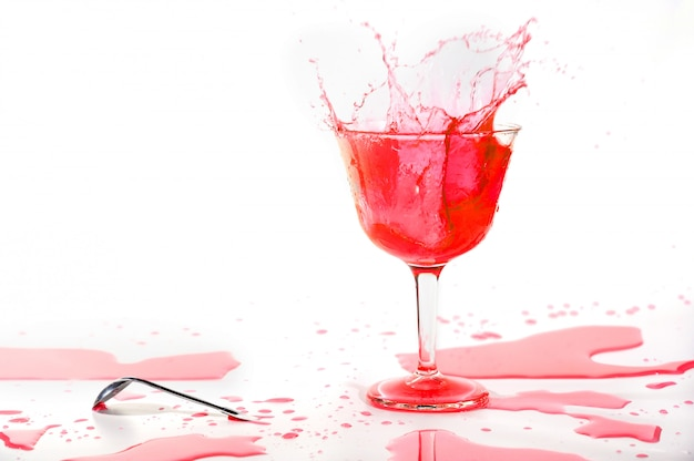 Red alcohol cocktail drink splash on white