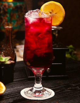 Red alcohol cocktail in glass with ice cubes and lemon slice