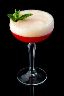 Red alcohol cocktail with mint isolated on black background