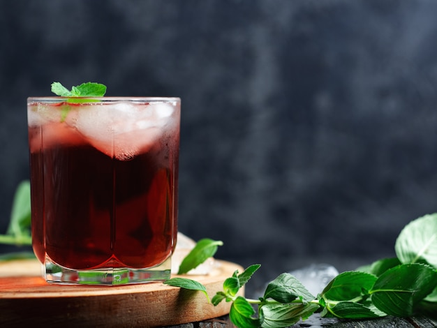 Red alcoholic cocktail with ice and mint in a glass