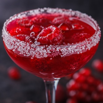 Red alcoholic cocktail with raspberry and pomegranate, in a glass glass. selective focus.