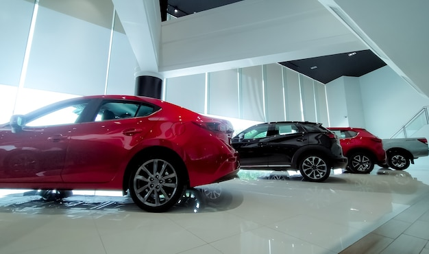 Красно-черный автомобиль припаркован в современном выставочном зале. автосалон и концепция автолизинга. автоматизированная индустрия. современный роскошный выставочный зал. новая машина припаркована в автосалоне. электрический автомобиль. интерьер салона.