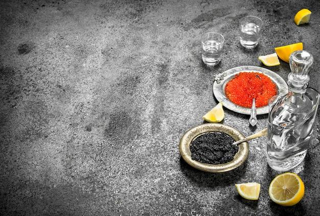 시골 풍 테이블에 보드카와 빨간색과 검은 색 캐 비어.