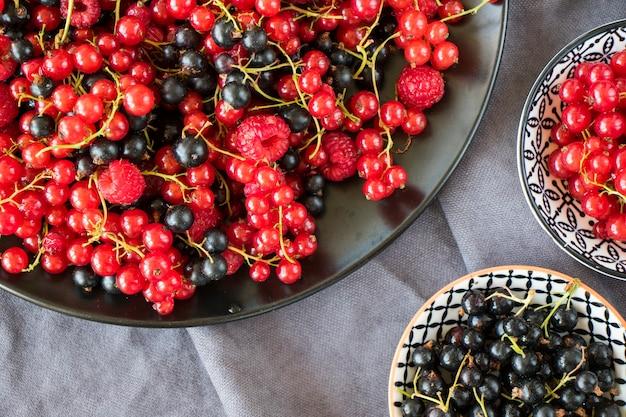 Красная и черная смородина и loganberries в миске на сером фоне ткани. большая группа красочных ягод.