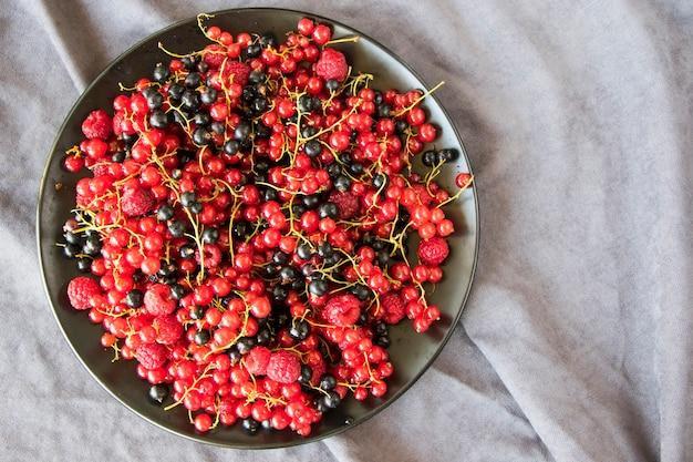 Красная и черная смородина и loganberries на черной тарелке и сером фоне ткани. большая группа красочных ягод.