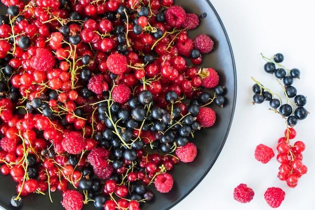 Красная и черная смородина и loganberries на черной тарелке и белом фоне. большая группа красочных ягод.