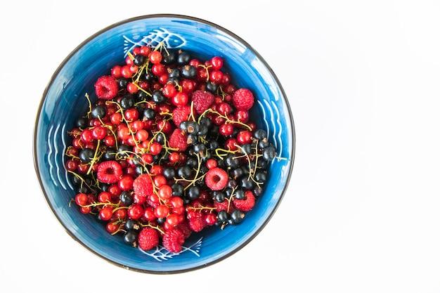 Красная и черная смородина и loganberries на синем фоне белой пластины. большая группа красочных ягод.