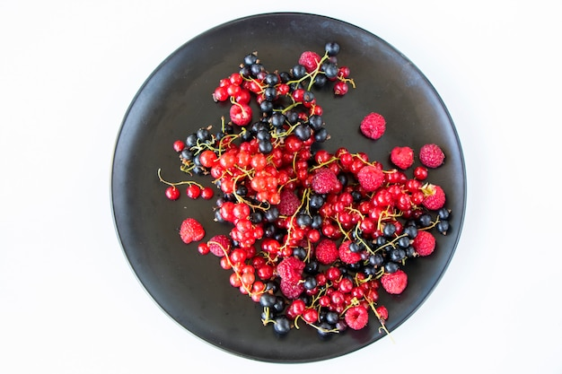 Красная и черная смородина и loganberries на белом фоне. большая группа красочных ягод.
