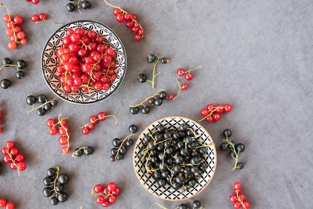 Красная и черная смородина в миске на сером фоне ткани. большая группа красочных ягод.