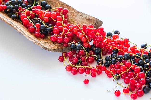 Красная и черная смородина на деревянном и белом фоне. разноцветные ягоды.