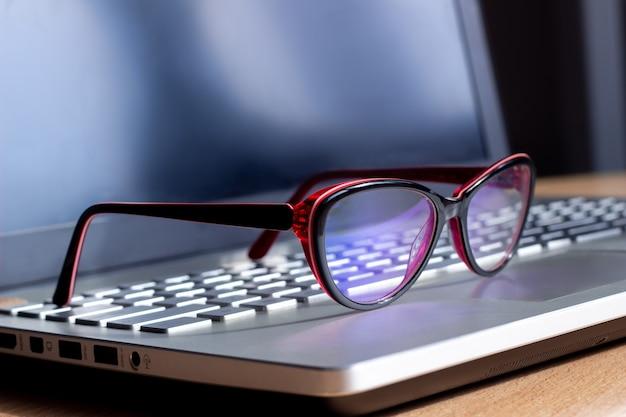 노트북 키보드에 파란색 필터가있는 컴퓨터에서 작업하기위한 빨간색과 검은 색 여성 안경. 안티 블루 라이트와 광선. 눈 보호