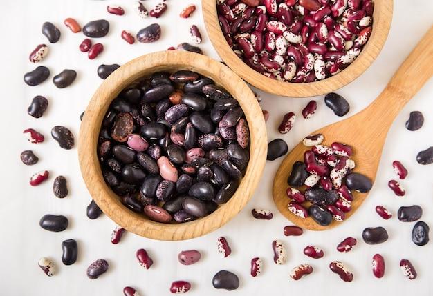 赤と黒のインゲン豆。木製の皿とスプーン。