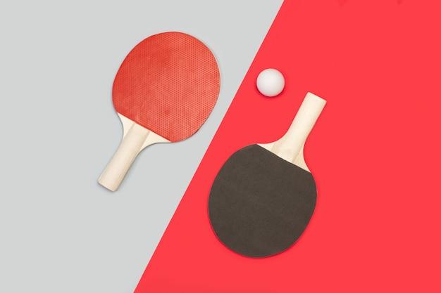 회색과 빨간색에 흰색 공이있는 빨간색과 검은 색 탁구 패들