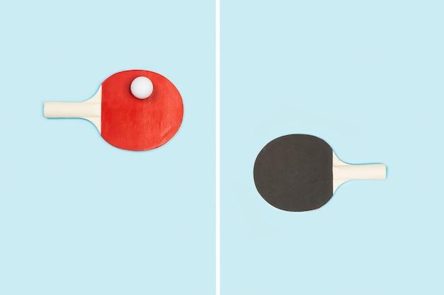 연한 파란색에 흰색 공이있는 빨간색과 검은 색 탁구 패들