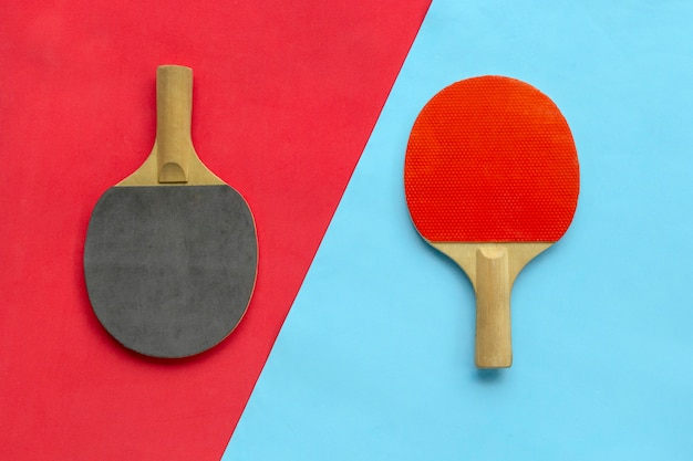 Красные и черные ракетки для настольного тенниса на синем и красном фоне.