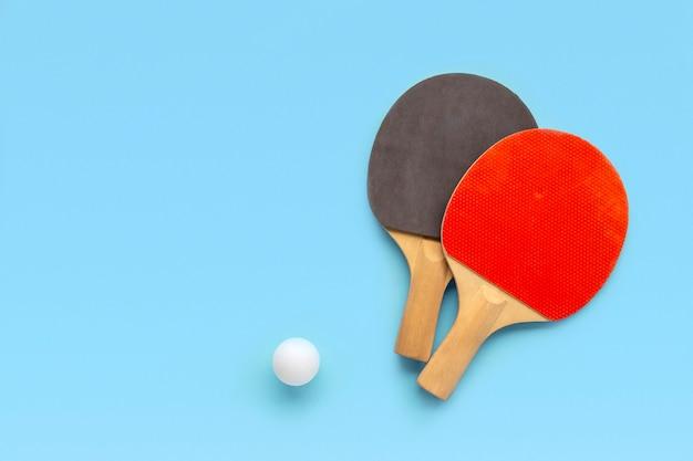 Красные и черные ракетки для настольного тенниса с мячом на синей стене. пинг-понг спорт