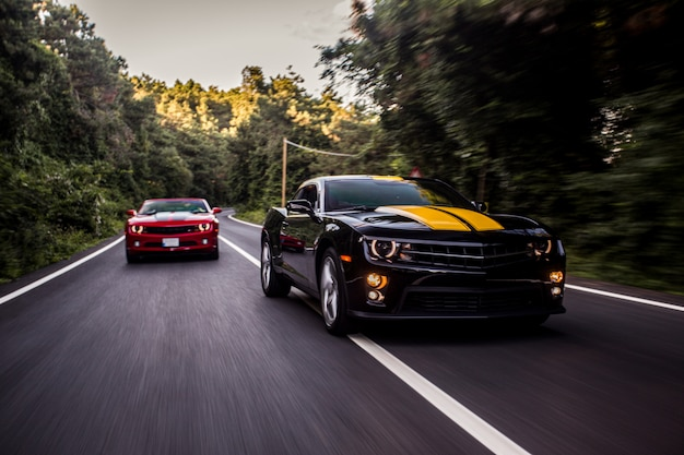 고속도로에서 경주하는 빨간색과 검은 색 스포츠 자동차. 무료 사진