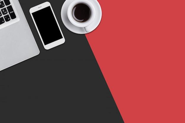 Красная и черная поверхность с компьютером, сотовым телефоном и чашкой вкусного кофе.
