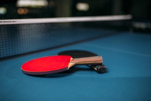 Красные и черные теннисные ракетки на столе против сетки