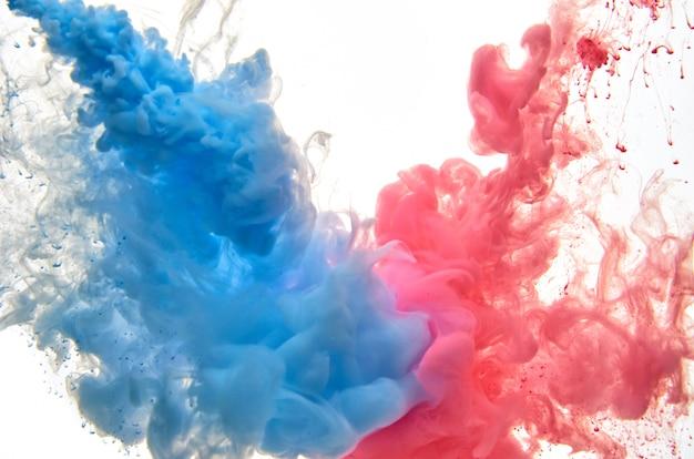 分離された白の水に赤と青のアクリルインク。抽象的な背景。