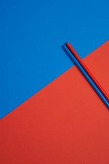 青と赤のテーブルに分離された赤と青の色鉛筆