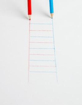 Красные и синие карандаши рисуют лестницу на белой поверхности. концепция развития.