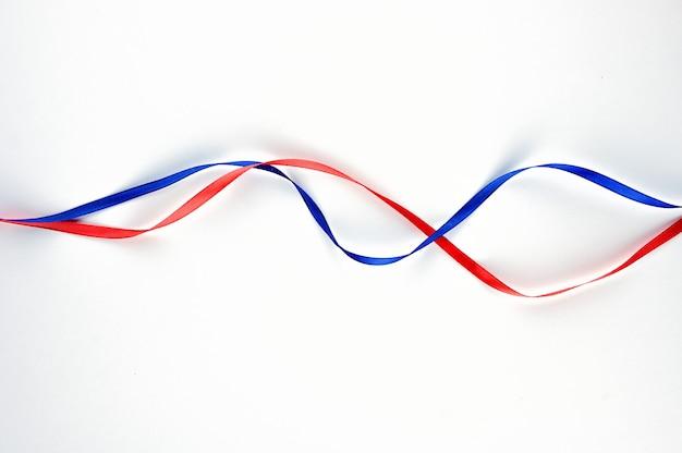 Красная и синяя лента переплетены. фото высокого качества