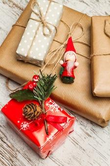 使い古した白い木製のテーブルに赤と茶色のクリスマスプレゼント