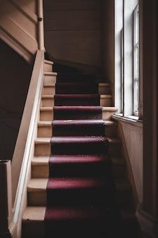 窓の近くの赤と茶色の階段