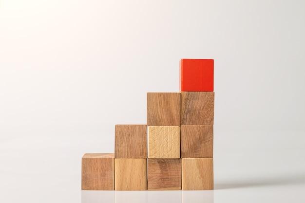 흰색 벽에 고립 된 빨간색과 갈색 나무 기하학적 도형 큐브