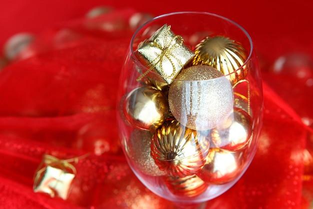 덩굴 유리와 그 안에 골드 크리스마스 장식이 있는 빨간색과 금색 크리스마스 배경. 크리스마스 장식이 있는 덩굴 유리