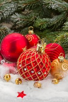 전나무 상록 나무 아래 눈에 빨간색과 금색 크리스마스 공