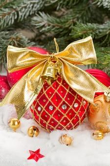 雪の中で弓と赤と金のクリスマスボール