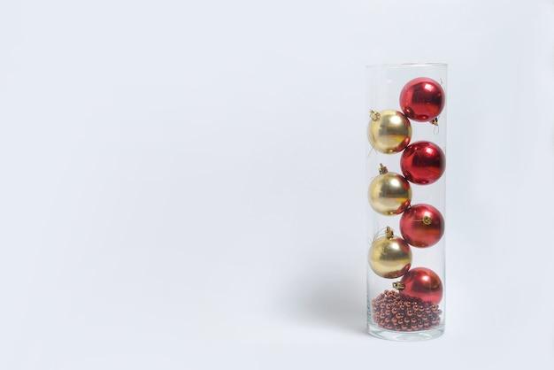 Красные и золотые рождественские игрушки в вазе на белом изолированном фоне. новогодний макет баннера. место для текста