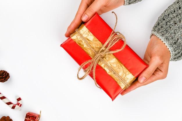 赤と金のギフトは手に包みます。ホワイトスペースにリボン付きニット。 diyギフトラップ。女性の手が包まれたプレゼントを差し上げます。クリスマスプレゼント。上からの眺め。